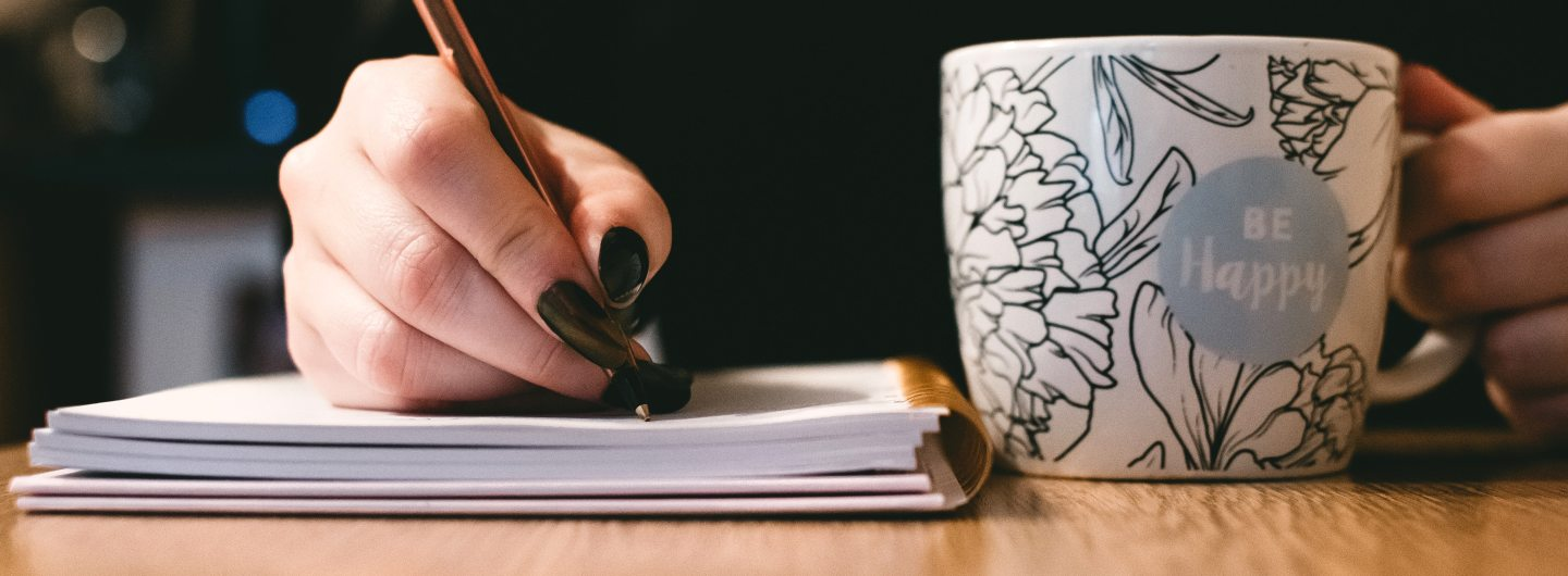 woman writing and holding coffee cup